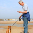Man with dog at the beach — Stock Photo