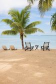 Tropical island with empty chairs — Stock Photo