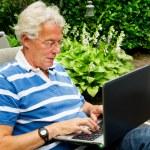 Senior man with laptop — Stock Photo