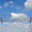 Sky behind the fence - Stock Photo
