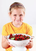 Child holding a bowl of fresh cherries — Stock Photo