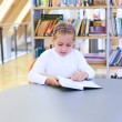 Child reading in library - Stock Photo