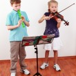 Kids playing flute and violin - Stock Photo