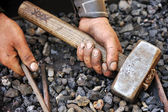Detail of dirty hands holding hammer and rod - blacksmith — Stock Photo