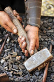 Detail of dirty hands holding hammer - blacksmith — Stock Photo