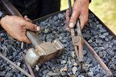 Detalj av smutsiga händer anläggning hammare och tång - smed — Stockfoto