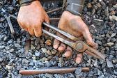 Detalle de sucias manos pinzas de sujeción - herrero — Foto de Stock