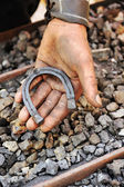 Detail of dirty hand holding horseshoe - blacksmith — Stock Photo