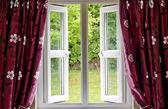 Open window draped in curtains, with a view — Stock Photo