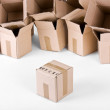Open boxes behind one sealed box infront - Stock Photo