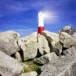 Lighthouse on rocks with light beams - Stock Photo