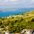 Fake toy village view over rolling hills and sea in the distance — Stock Photo