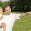 Cute baby girl in fathers arms — Stock Photo