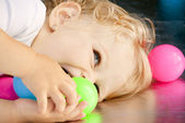 Baby girl playing with balls — Stock Photo
