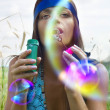 Woman blowing soap bubble - Stock Photo