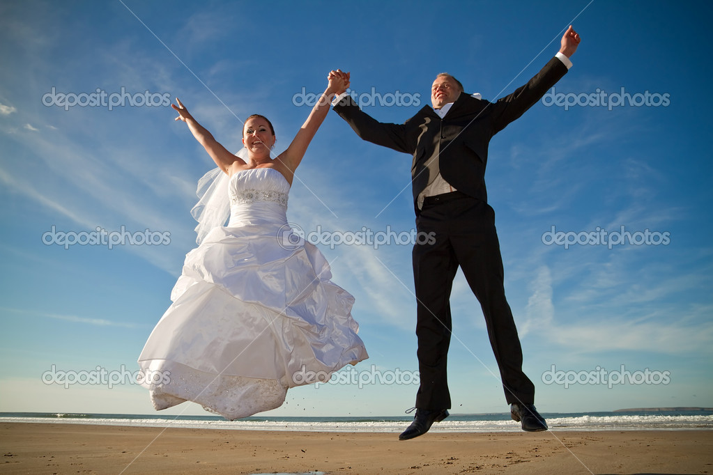 Wedding couple jumping on the beach — Stock Photo #5588465