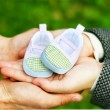 Pregnant couple holding a little boot in their arms. Close-up. - Stock Photo