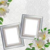 лилии на белом фоне с кружевами и 2 серебряные рамы — Стоковое фото