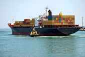 The small tugboat accentuates the size of the large container sh — Stock Photo
