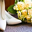 Wedding rings with bouquet and high heel shoes — Stock Photo