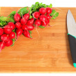 Radishes and knife on wooden board — Stock Photo