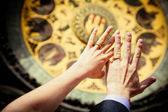 Hands of newly married on clock background — Stock Photo