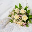 Wedding bouquet on wedding dress - Stock Photo