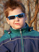 A boy with glasses with a grimace on his face — Стоковое фото