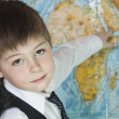 The boy is studying the physical map of the world — Stock Photo