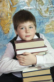 Schoolboy with a stack of books on a background map of the world — Stock Photo