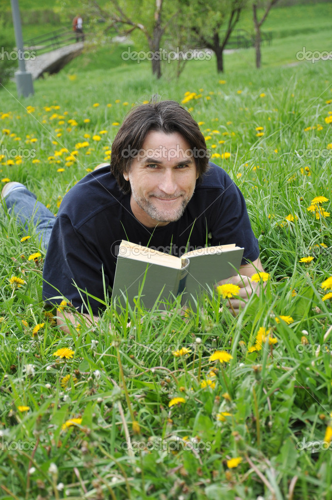 A man reads a book in the park  Stock Photo #5655682
