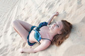 Beautiful Woman in a bathing suit lying on the sand — Stock Photo