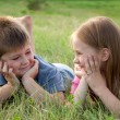 Funny Boy and girl lying on grass — Stock Photo