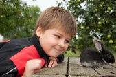 A boy with a rabbit in the garden at the cottage — Stock Photo
