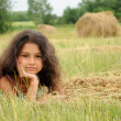 Royalty-Free Stock Photo: Beautiful girl in a field on a background of straw