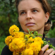 Portrait of a woman with yellow flowers — Stock Photo