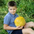 Stock Photo: A boy with a large melon in his hands