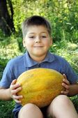 A boy with a large melon in his hands — Stock Photo