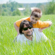 Dad and son relaxing on green grass — Stock Photo #6703305