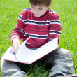 A boy reads a book in the park — Stock Photo #6720136