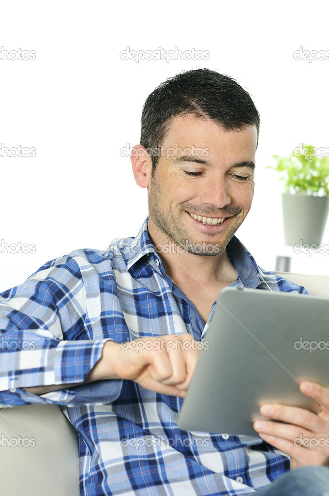 Attractive relaxed and positive man is surfing on his tablet  Foto Stock #5458894