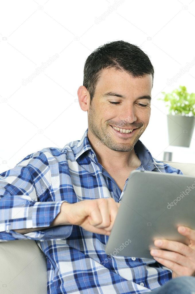 Attractive relaxed and positive man is surfing on his tablet  Stock Photo #5458894