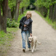 Blond woman walking with her golden retriever dog in the park — Stok fotoğraf