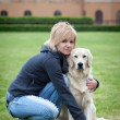 Blond woman walking with her golden retriever dog in the park - Stock Photo