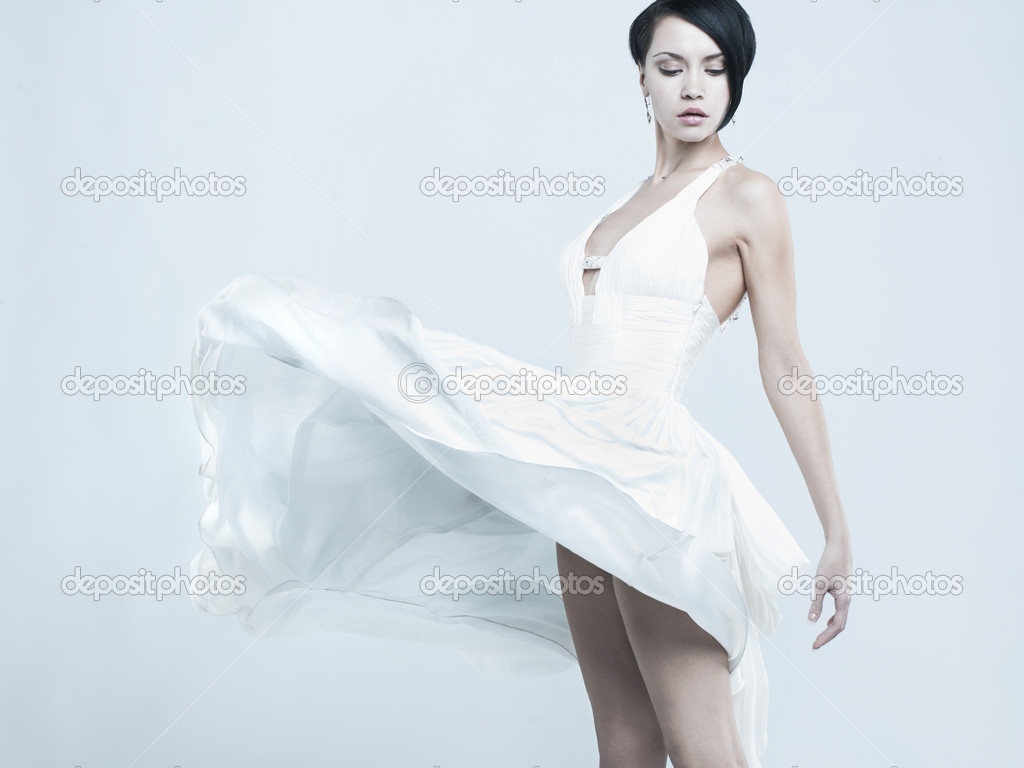Fashionable photo of beautiful young lady in a billowing white dress  Stock Photo #5481036