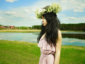 Beautiful girl wearing a wreath of wildflowers — Stock Photo