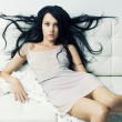 Beautiful woman sitting on a sofa - Stockfoto