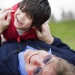 Father playing with disabled son on grass at park — Stock Photo