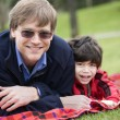 Stock Photo: Father lying on blanket with disabled son at park