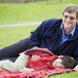 Stock Photo: Father lying on blanket with son at park